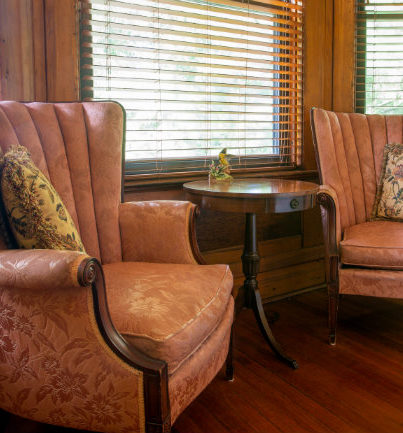 Two wing back chairs placed in front of bay window