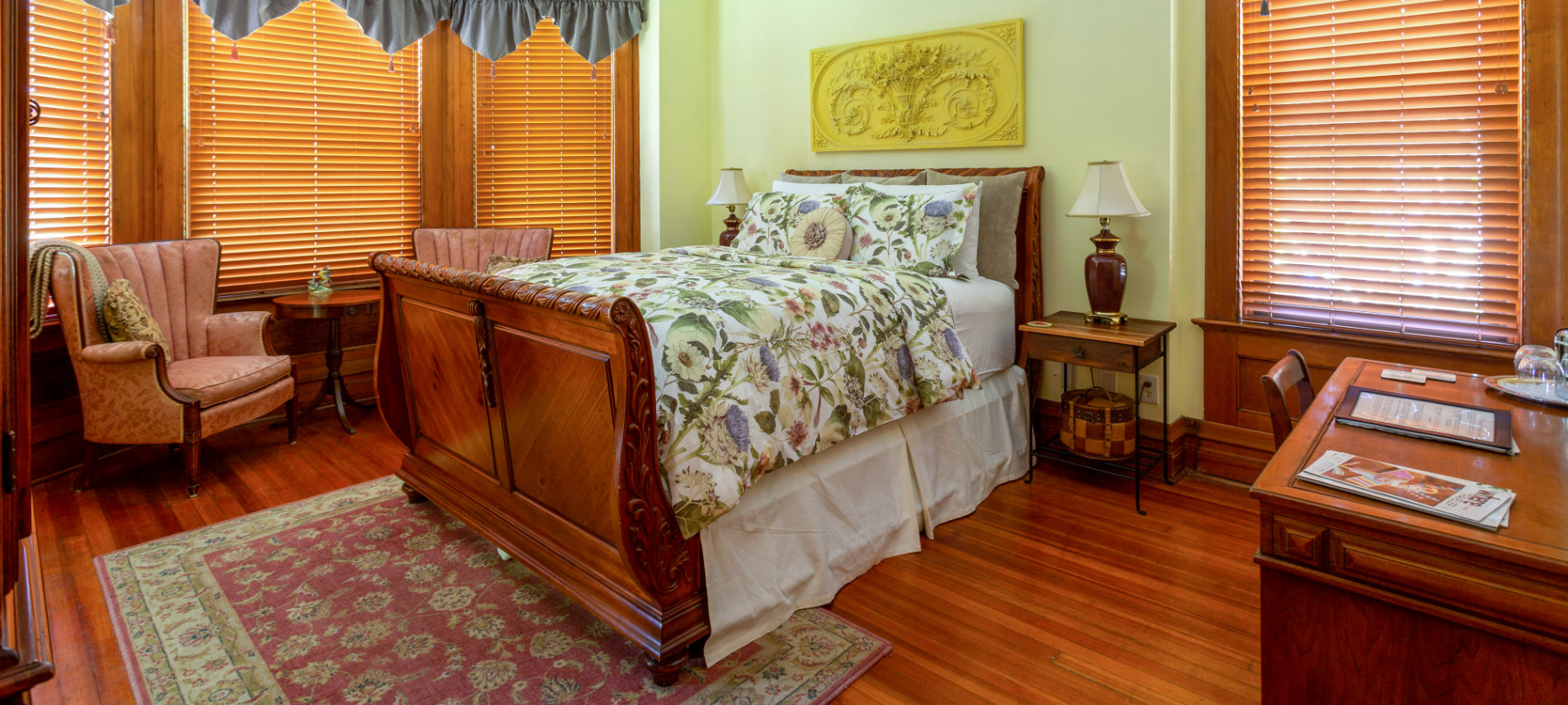 Sleigh bed with floral comforter, two wingback chairs in front of bay window