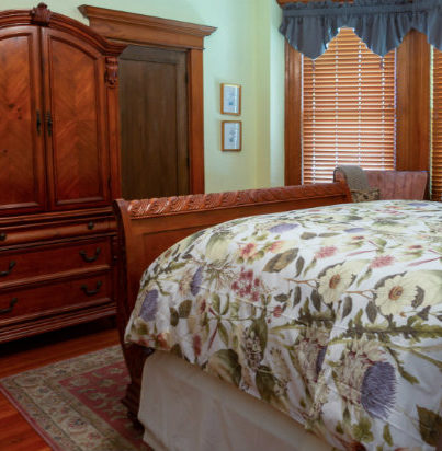 Sleigh bed with floral comforter, large armoir