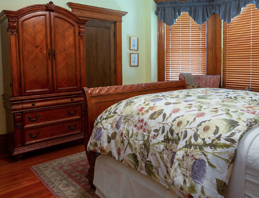 Cherry sleigh bed with floral comforter, wingback chairs in front of bay window