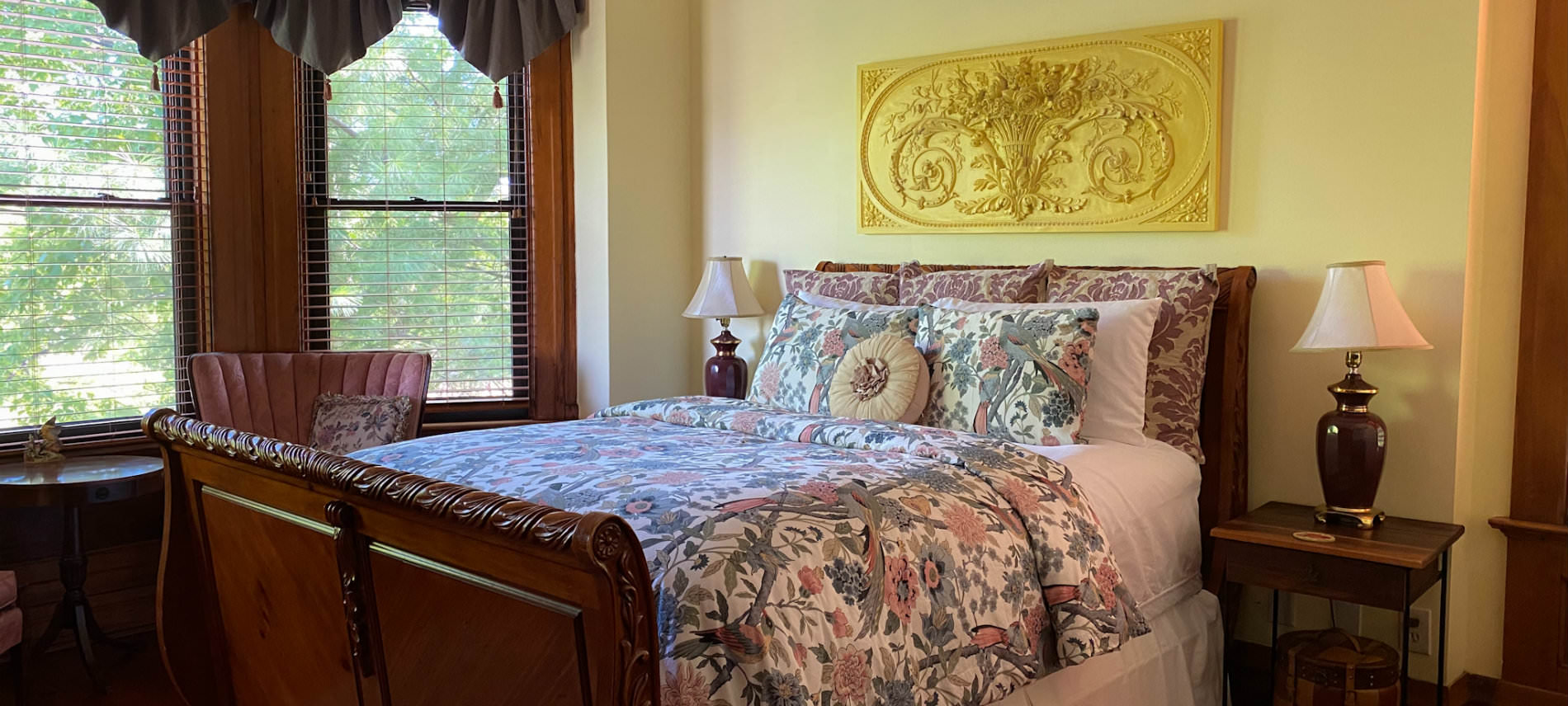 Botanical Garden room with floral bedspread, sitting area in front of bay windows