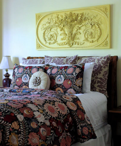 Close up of bed with flower embroidery comforter and large pillows