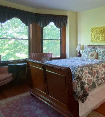 Sleigh bed in front of wingback chair seating area by bay windows