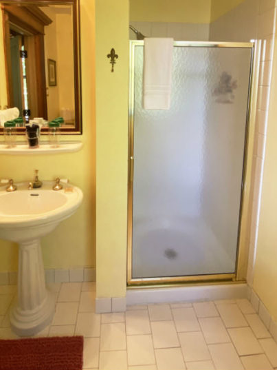 Bathroom view with pedestal sink and walk in shower