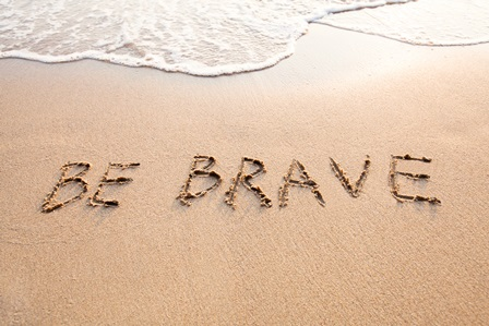 "Sandy beach with receding wave and the words ""Be Brave"" written in the sand"