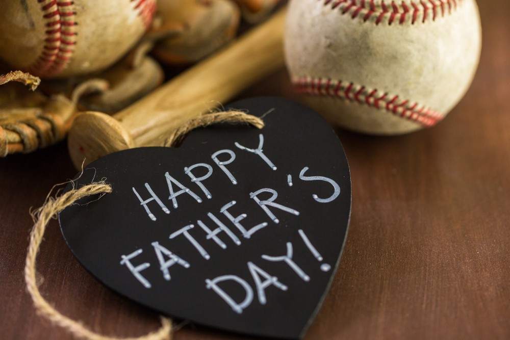 Happy Father's Day written in chalk in front of a baseball glove and ball