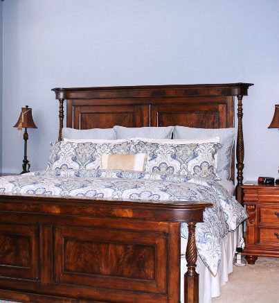 Large Oak King bed with Paisley comforter and lamp on bedside table