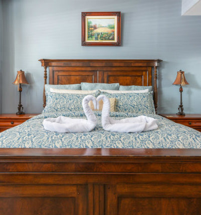 Mahogany bed with blue comforter and swan towels