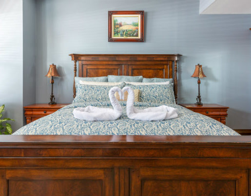 Mahogany wood bed with Paisley comforter and bedside table
