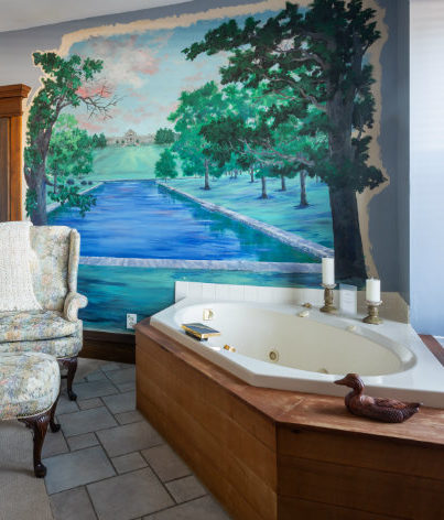 Two person jetted tub in front of painted mural and wing back chair