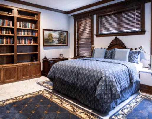 California King bed with fleur de lys comforter, work desk, book cases