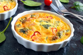 Frittata with fresh vegetables and spinach. Italian omelet in ceramic forms on a black background