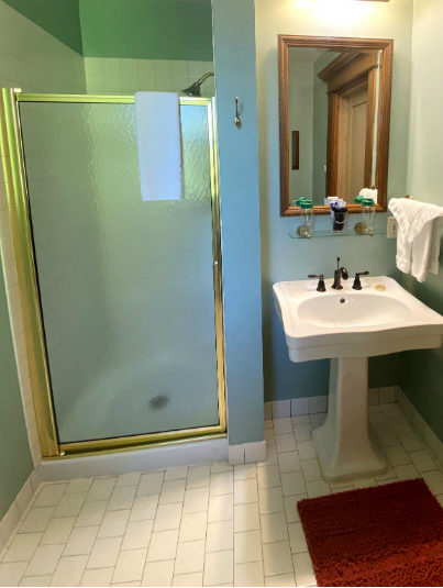 Bathroom with a pedestal sink and walk in shower