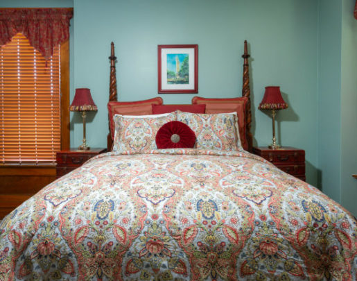 Four poster bed with multi color comforter. Red pillows and throw pillows. Side table and chairs.
