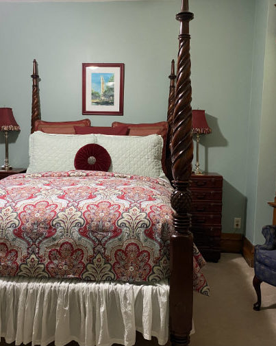 4 poster bed with red floral duvet and pillows on the bed