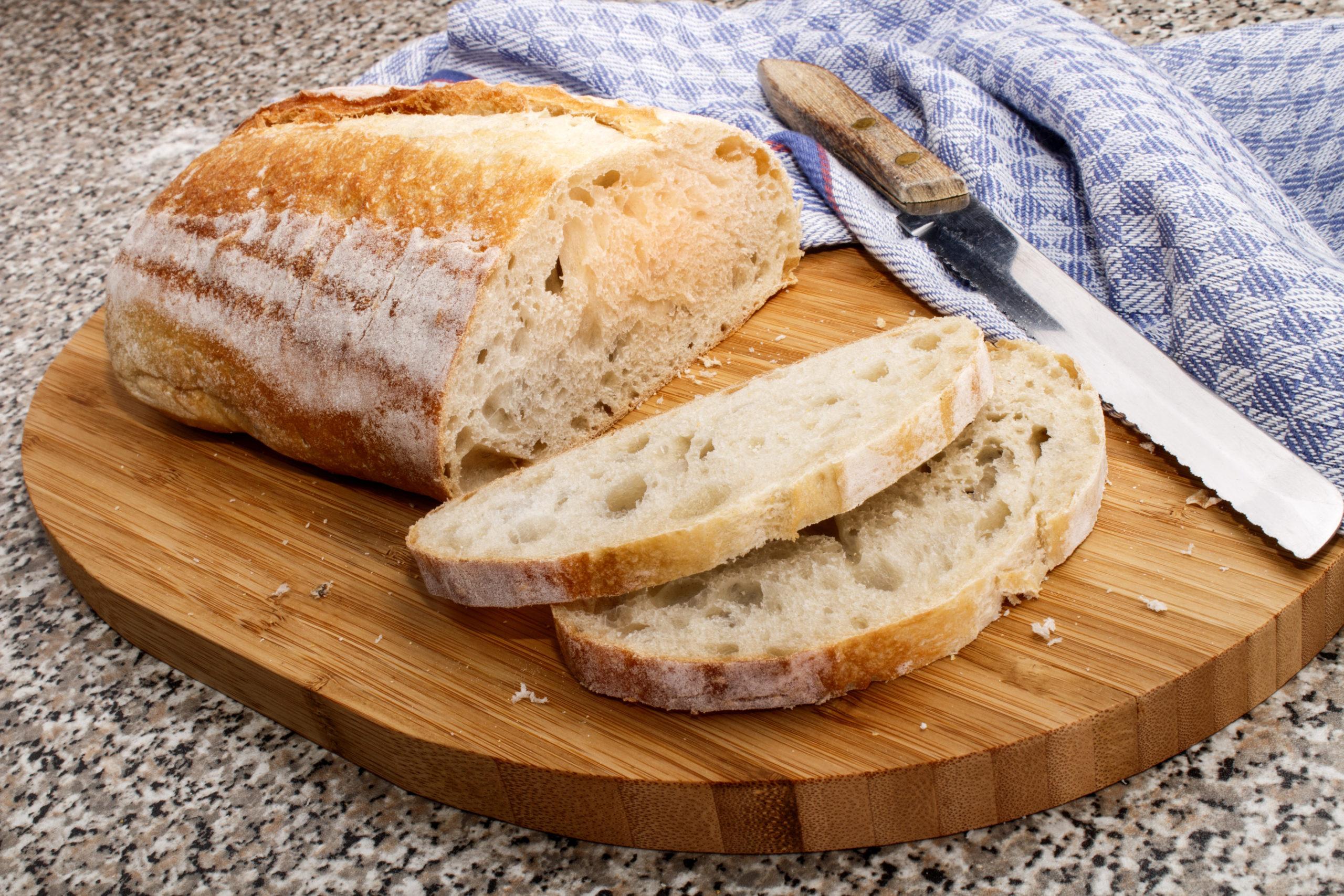 Sliced fresh sourdough bread on a bread board with knife