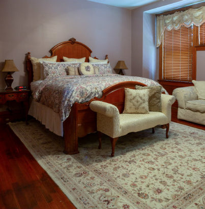 King size bed with floral comforter bench with pillows