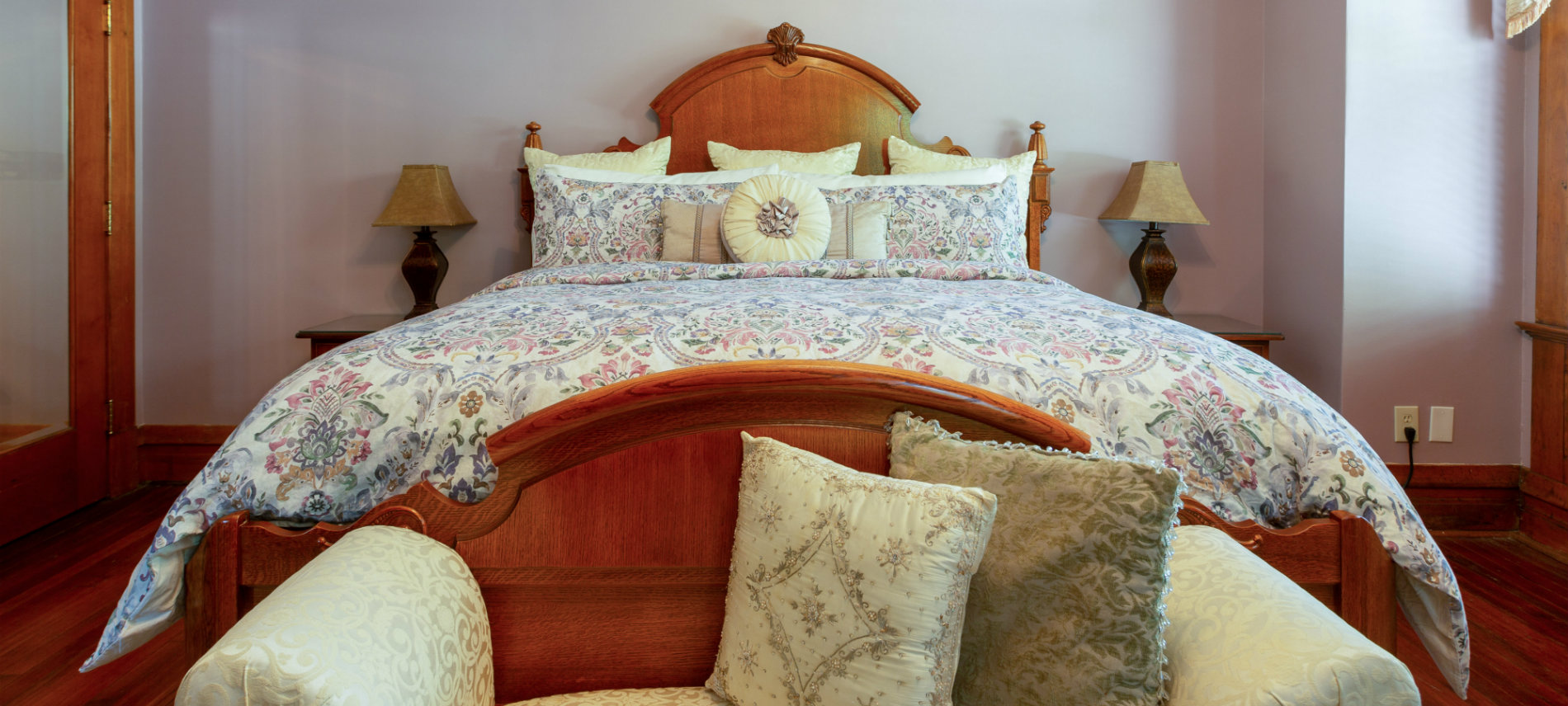 Large king bed with floral comforter, love seat and bedside table with lamp