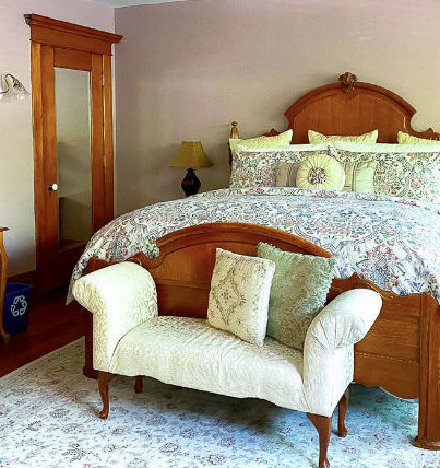 Large king bed with floral comforter, seat at the end of the bed, desk and mirrored closet
