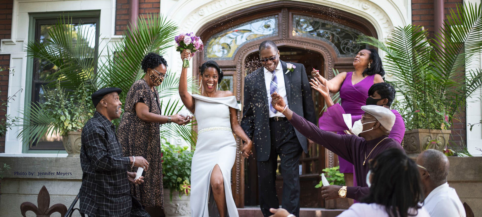 Bride and Groom exiting Mansion front door with guests throwing lavender