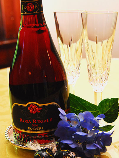 Bottle of Rosa Regale 2006 wine with blue hydrangea flower and two champagne flutes.