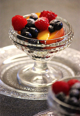 Round glass serving bowl with mixed berries and peaches sitting on a glass serving plate.
