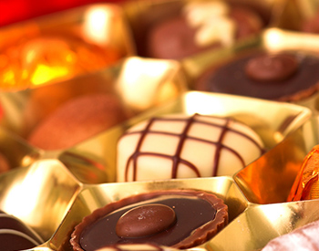 Gourmet white and dark chocolates with carmel sitting in gold wrappers.
