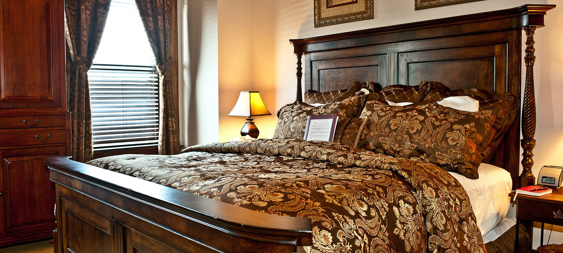 Mahogany wood bed with brown and gold comforter. Brown and gold drapes and mahogany armoire.