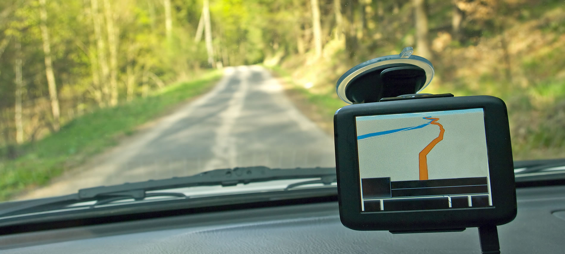 A car drving down a road with green trees and grass using a GPS on dash.