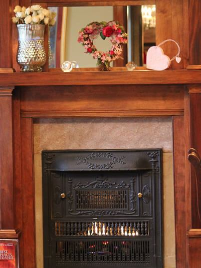 Fireplace with black cast iron grate and roaring fireplace within.
