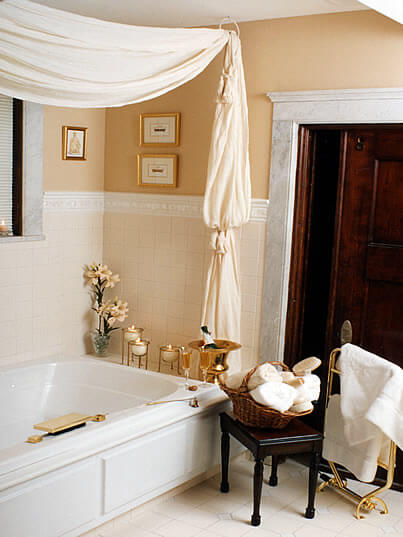 Jetted tub with lit candles, white canopy, and basket with white rolled towels.