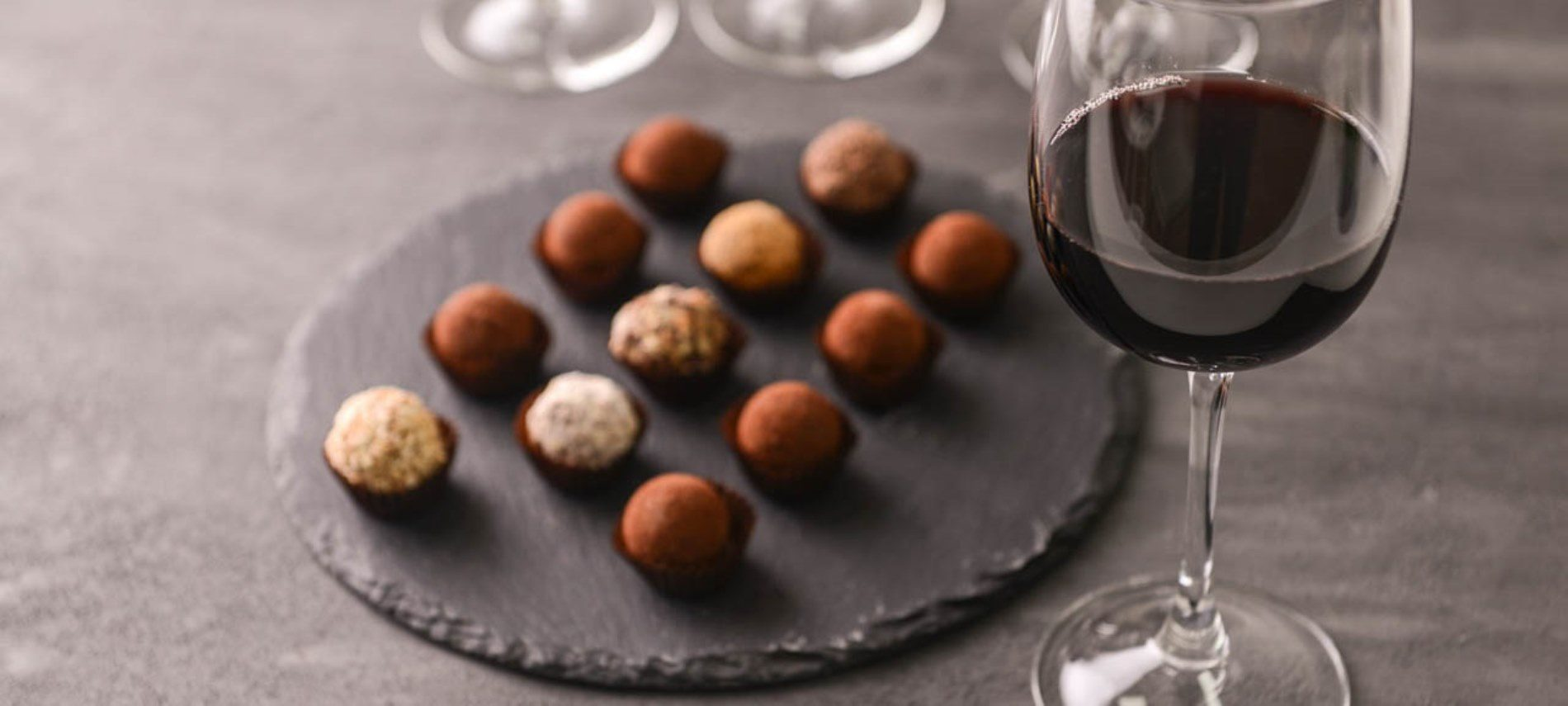 Delicious chocolate truffles and red wine on grey background